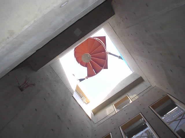 建物屋根の開口部分から螺旋階段を吊るし下ろす
