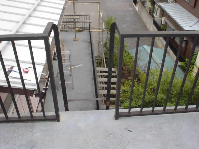 物干し場から階下のバルコニーを見下ろす