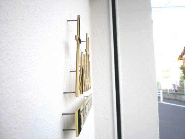 真鍮サインの裏側にスタッドを固定し、建物に取り付ける