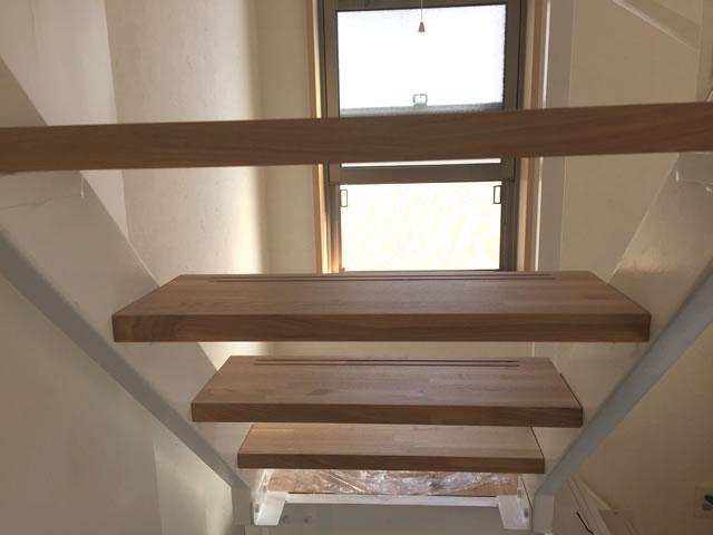 木の段板が浮いているような鉄骨階段