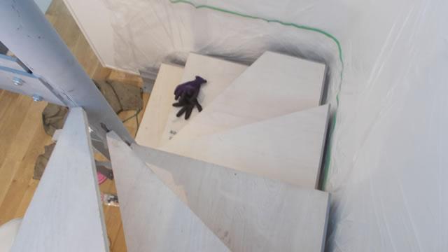 仮の木板で養生される室内の鉄階段